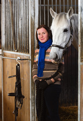 Woman and white horse inside a stall, vertical format
