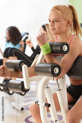 Young girl working out on weight machine