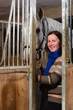 Smiling woman and white horse inside a stall, vertical format