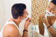 Asian man shaving in front of mirror
