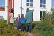Junge Familie vor Eigenheim