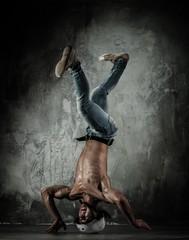 Young b-boy man with naked torso doing brake dancing movements
