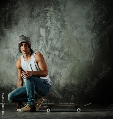 Young man in hat and jeans sitting near skateboard