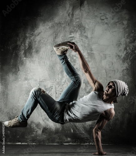 Wall mural Young b-boy man doing brake dancing movements