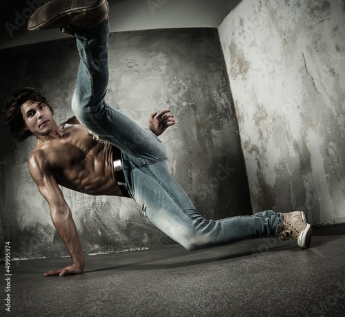 Young b-boy man with naked torso doing brake dancing movements