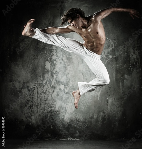 Young b-boy man with naked torso performing jumps