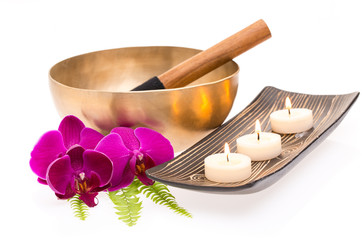 Klangschale mit Farn, Orchidee und Kerzen auf weißem Hintergrun