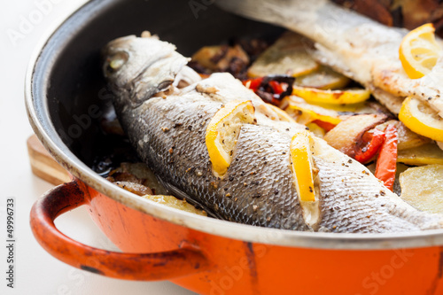 Cooked seabass with lemon, potatoes and pepper in a pan.