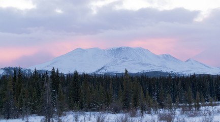 Sunset glow behind winterly Little Peak YT Canada