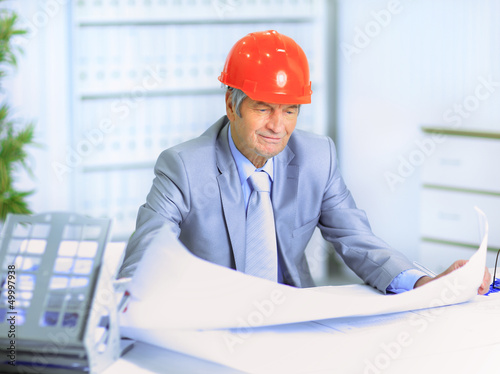 Engineer at the age of considering plans drawing