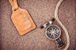 Vintage compass and leather tag on sand background
