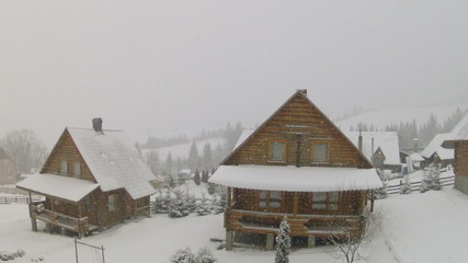 Wooden houses and falling snow with moving camera