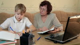 Grandma helping grandchild doing homework