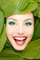 woman beauty face with green leaves frame