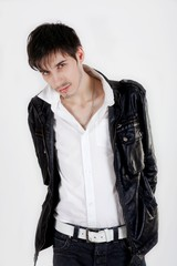 jeune homme séduisant en blouson noir sur fond blanc