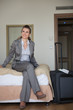 Happy business woman sitting on bed in hotel room
