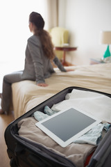 Closeup on bag with tablet pc and business woman on bed