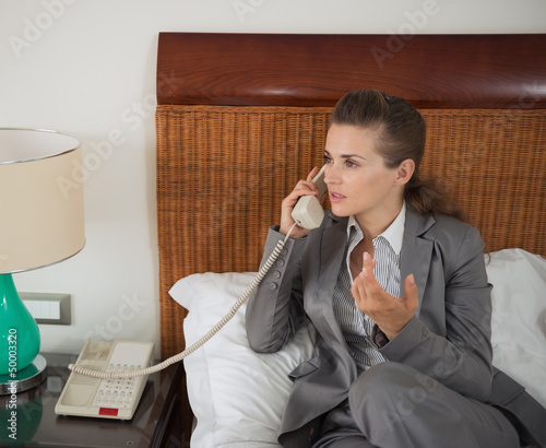 Business woman talking phone in hotel room