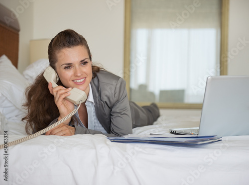 Business woman laying in bed with laptop and talking phone
