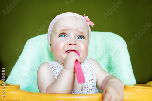 crying child with spoon in mouth