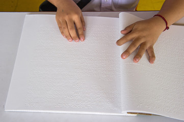 fingers and braille. blind people read a book in braille.