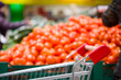 Shopping cart and bunch of tomatoes on boxes in supermarket