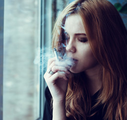 beautiful girl smokes under stress, wanting to relax