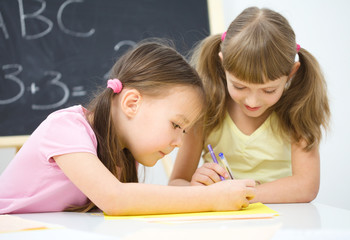 Little girls are writing using a pen