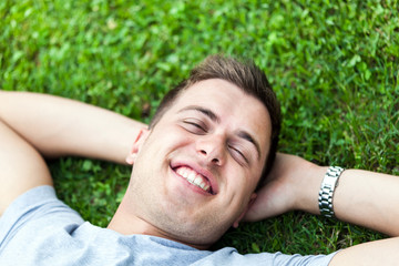 Man laying on the grass with hands behind head