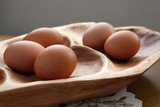 Five fresh brown eggs on wood platter