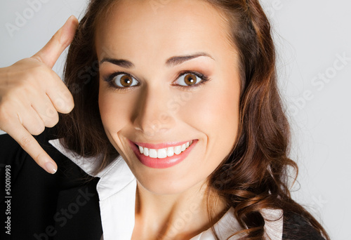 Businesswoman with call me gesture, over gray
