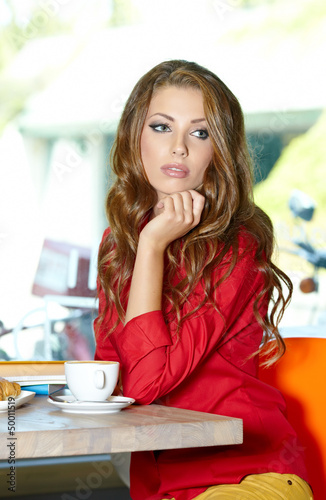 Beautiful young college student on a cafe.