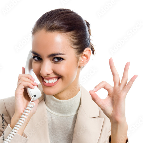 Businesswoman with phone showing okay sign