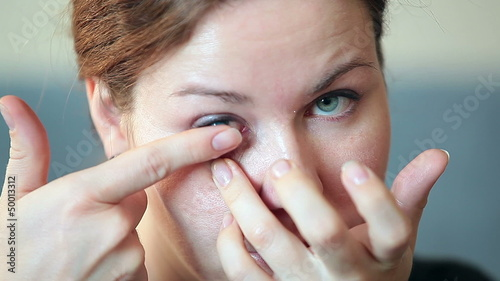 Young woman inserting blue contact lens in eye