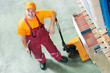 waregouse worker with fork pallet truck