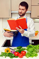 handsome young man reading cookbook attentively