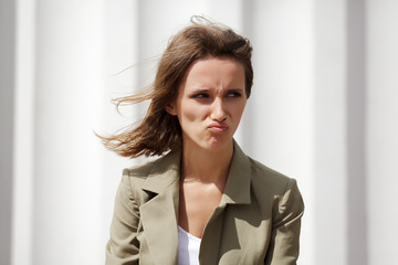 Angry young woman against a white wall