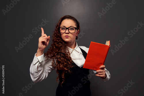 student in glasses holding book