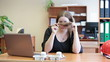 Lazy woman boring at the desk and turning her hair on fingers