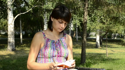 young pregnant woman leafs through a notepad