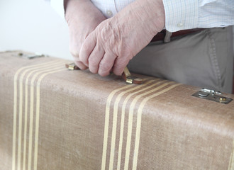 man grips a vintage suitcase with both hands