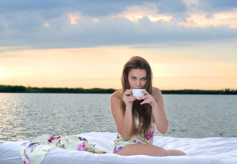 The girl woke up in a bed on water and drink cup of coffee