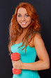 Red haired woman with a dumbbell
