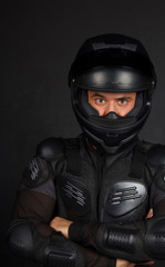 Self confident biker with a crossed hands in a dark background