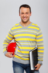 Happy businessman with helmet and folder on the white background