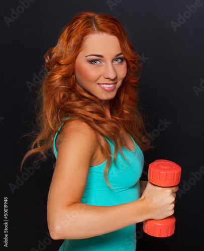 Woman with red dumbbells posing on the photoshoot