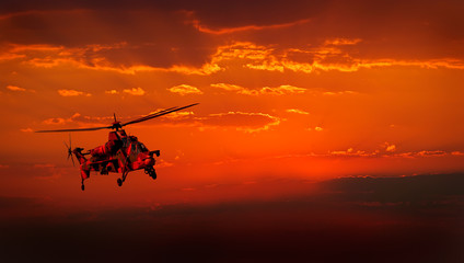 Military helicopter in flight against a dramatic red sky