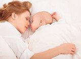 mother embraces the newborn baby  sleeping together in bed