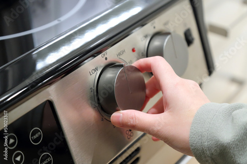 Woman turning on the oven
