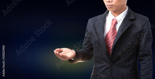 man wearing black suit post seem like holding something in hand